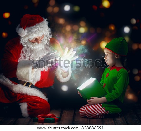 Cute little girl and Santa Claus opening a magic gift box. - stock photo