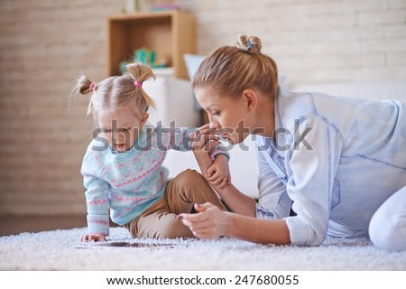 Cute little girl and young woman using digital tablet while spending time at home - stock photo