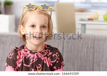 Cute little girl at home with funny star shaped glasses, smiling. - stock photo