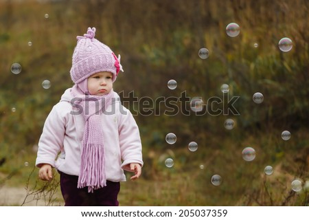 cute little girl at park catching bubbles - stock photo