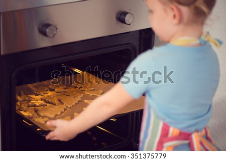Cute little girl baking Christmas cookies in oven at home - stock photo