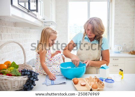 Cute little girl baking with her grandmother at home - stock photo