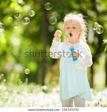 Cute little girl blowing bubbles in the park - stock photo