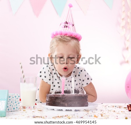 Cute little girl blowing colorful candles on chocolate cake. Concept of birthday celebration and dream.