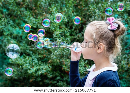 cute little girl blowing soap bubbles in the park