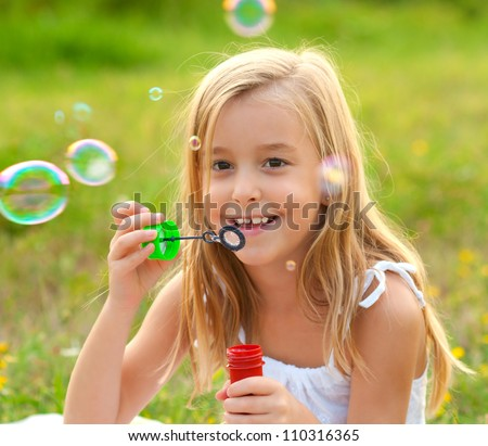 Cute little girl blowing soap bubbles on the meadow on sunny summer day. - stock photo