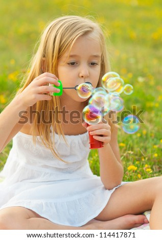 Cute little girl blowing soap bubbles while sitting on the meadow on beautiful spring day. - stock photo