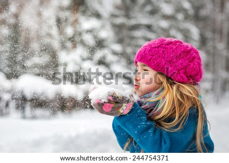 Cute little girl blows snow from hands. Close up - stock photo