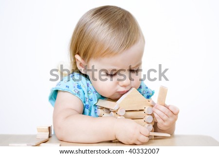 Cute little girl building wooden house