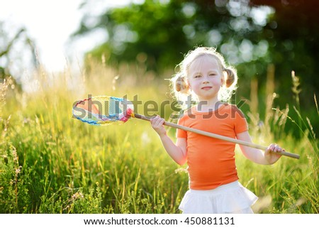 Cute little girl catching butterflies and bugs with her scoop-net on beautiful sunny summer day - stock photo