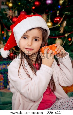 Cute little girl checking gift box in front of christmas tree - stock photo