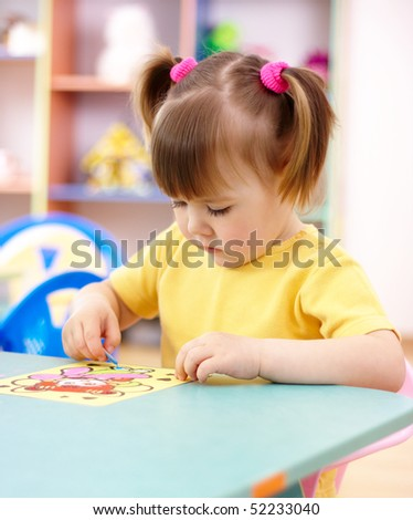 Cute little girl coloring a picture in preschool - stock photo