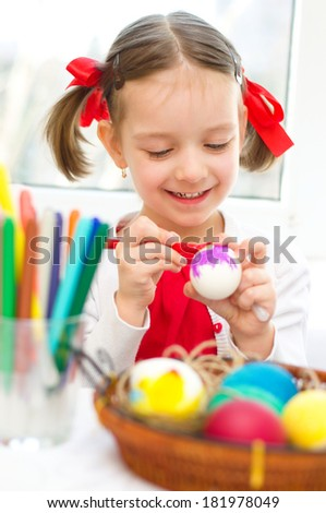 cute little girl coloring eggs for Easter