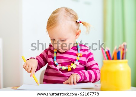 Cute little girl coloring with pencils at home - stock photo