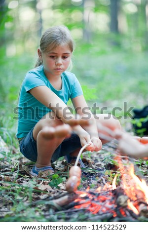 Cute little girl cooking sausages on campfire in forest - stock photo