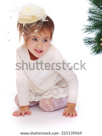 Cute little girl crawls on knees at the Christmas tree-Isolated on white background