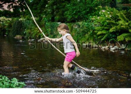 Cute little girl crossing river with cane, children outdoor games