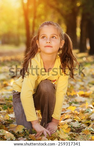 Cute, little girl crouch in the autumn park, looking up.Shallow doff, sunset light, lens flare - stock photo