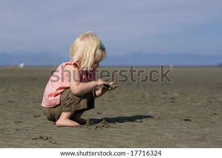 Cute little girl crouched on on beach holding sand in her hands.