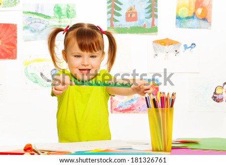 Cute little girl cutting and gluing color paper in the preschool art class