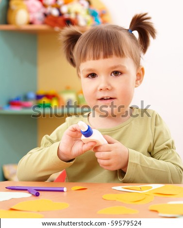 Cute little girl doing arts and crafts in preschool - stock photo