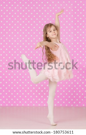Cute  little girl doing ballet  exercises on pink background - stock photo