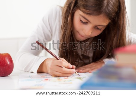 Cute little girl drawing. Elementary age. - stock photo