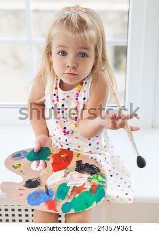 Cute little girl drawing paints holding palette and brush - stock photo