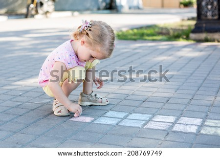 cute little girl drawing with chalk on the pavement - stock photo