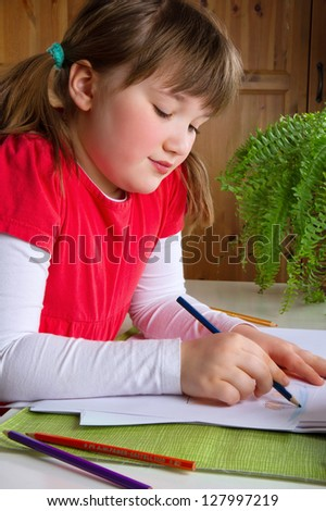 Cute little girl drawing with color pencils at her desk
