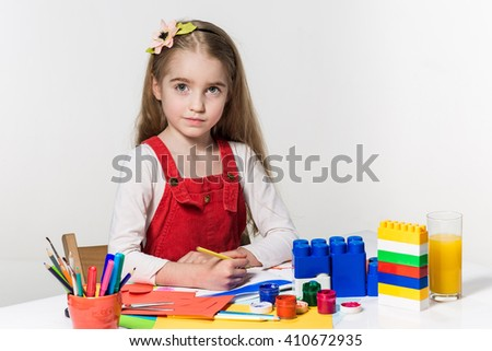 Cute little girl drawing with paint and paintbrush at home - stock photo