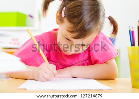 Cute little girl drawing with pencils at home - stock photo