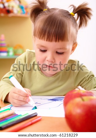 Cute little girl draws with felt-tip pen in preschool - stock photo
