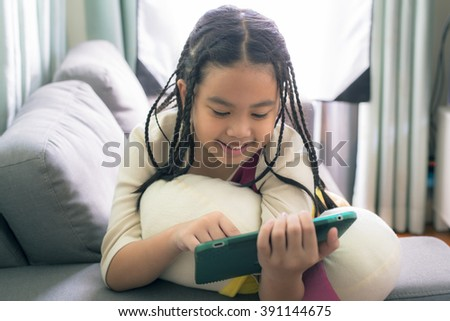 Cute little girl,dreadlocks hair style ,playing with computer at home laying on sofa  - stock photo