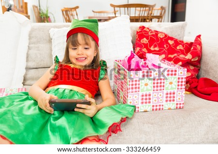 Cute little girl dressed as Christmas elf holding mobile phone - stock photo