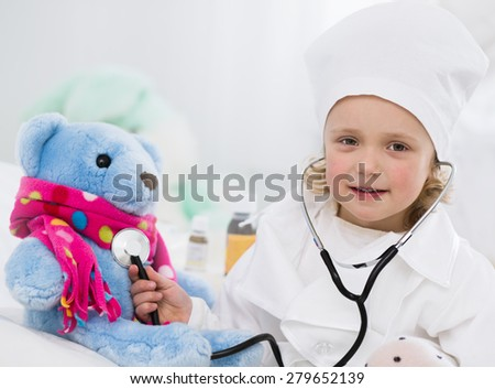 cute little girl dressed as doctor playing with toy - stock photo