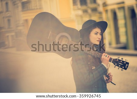 Cute little girl dressed in a man's suit and extravagant hat, holding a guitar on his shoulder, a street musician - stock photo