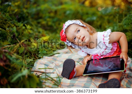 cute  little girl dressed in a multicolored crochet dress sitting on a plaid blanket in the park playing a computer game on the tablet - stock photo