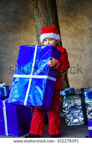 Cute little girl dressed in red santa hat with big gift boxes
