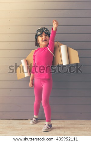 Cute little girl dressed like a pilot with toy wings is smiling and looking upward, standing against gray wall - stock photo