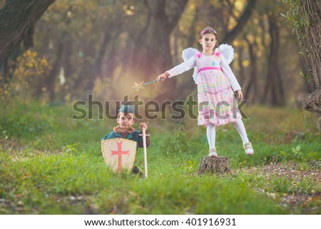 Cute little girl dressed up as a fairy playing with a boy dressed up as a knight sitting in a magical forest - stock photo