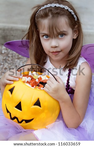 Cute little girl dressed up as a purple fairy eating candy from a pumpkin Halloween bucket.