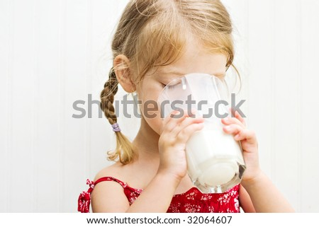 Cute little girl drinking a large glass of milk - stock photo