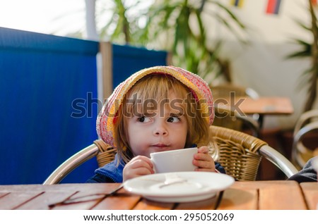 Cute little girl drinking. Attractive female child holding coffee cup. Sweet preschooler kid acting grown up. Childhood concept. Model Release