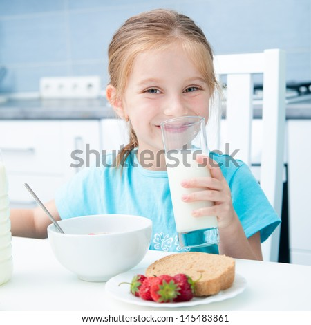 cute little girl drinking milk in the kitchen - stock photo