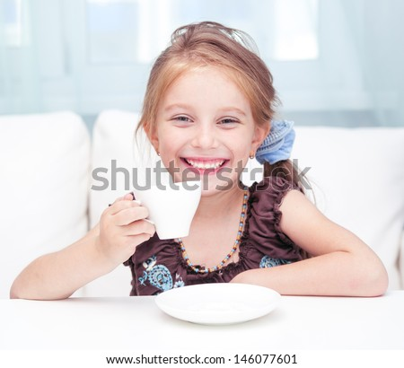 cute little girl drinking tea in light room at home - stock photo