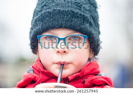 Cute little girl drinking water/juice hot chocolate - through a straw outdoors - very shallow depth of field - stock photo