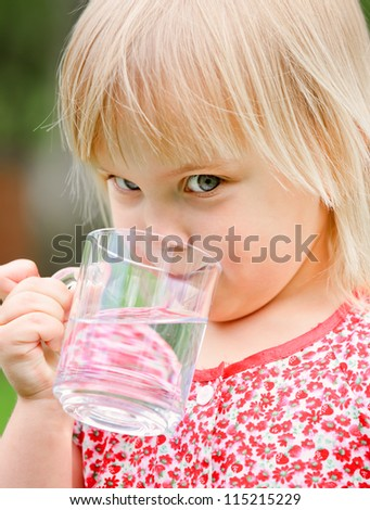 Cute little girl drinking water outdoors - stock photo
