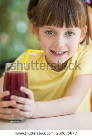 Cute little girl drinks  juice using drinking straw - stock photo