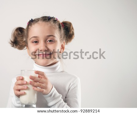 Cute little girl drinks milk - stock photo
